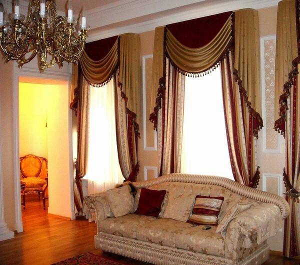 окна в клаасической гостиной оформлены золотисто-бордовыми шторами
