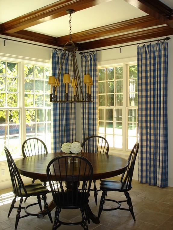 столовая зона на веранде с клетчатыми шторами на окнах