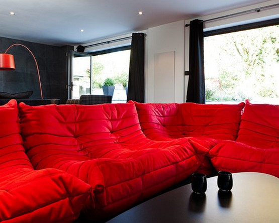 черные шторы к черным стенам и акцент на красном диване в гостиной комнате
