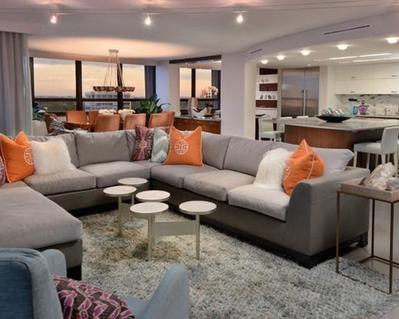 серый диван и оранжевые подушки
