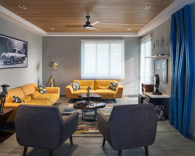 желтиый диван на синем фоне стены